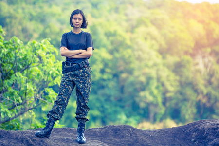 disciplined: Female soldier on the nature background