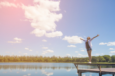 Woman spreading arms to sky Stock Photo