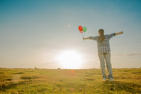 gesturing: Young girl spreading hands and holding balloon and inspiration facing the sun Stock Photo