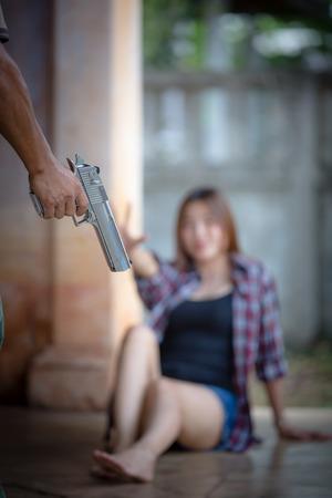 Violence against women: Man threatening beaten up girl with gun Stock Photo