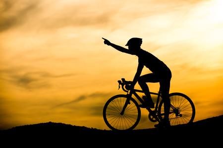 Silhouet van de mens op de fiets met zonsondergang achtergrond Stockfoto - 68326399