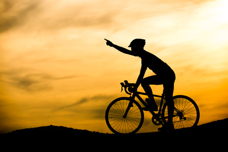 silhouette of man on bicycle with sunset background