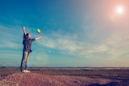 Young girl spreading hands and holding balloon and inspiration facing the sun Stock Photo