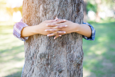 Close-up of hands hugging tree 版權商用圖片