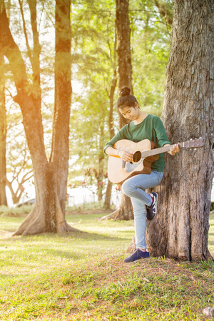 prety: Young asian girl in forest with guitar, selective focus