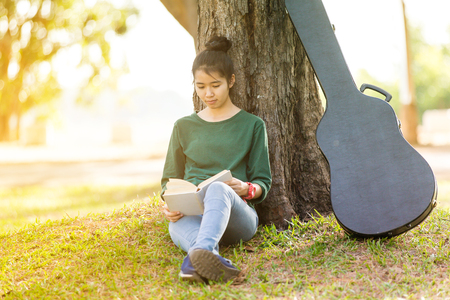 Beautiful young asian woman sitting and reading book in a park