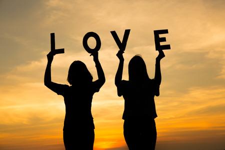 Silhouette love in hand. Background sunrise Stock Photo