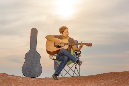 asian men playing guitar outdoor
