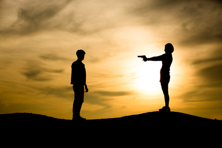 Silhouette  woman pointing at the man on the sunset background Stock Photo
