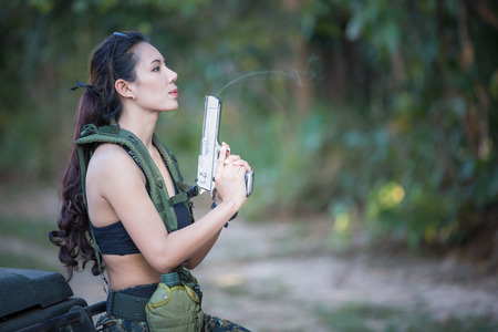 Beautiful woman soldier with a pistol
