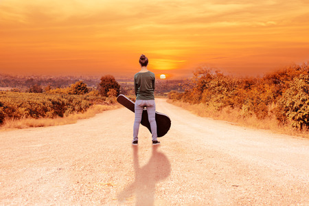 asian girl with guitar case on sunset background