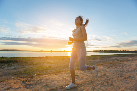 hacer footing: asian woman runing along the sea coast
