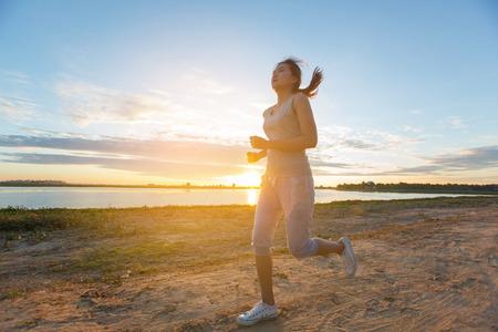 jog: asian woman runing along the sea coast