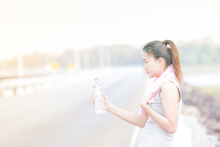 high key: portrait of young woman drinking water after sporting,high key