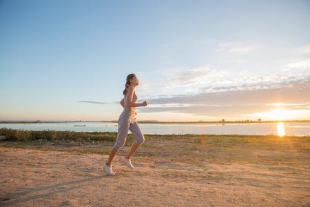 runing: asian woman runing along the sea coast