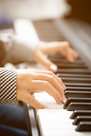 Close up of woman hands playing piano Stock Photo