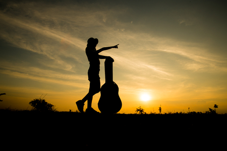 silhuette of woman with guitar case on sunset background