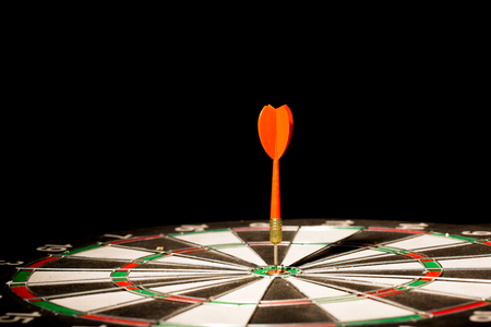 red darts hitting the center of target on black background