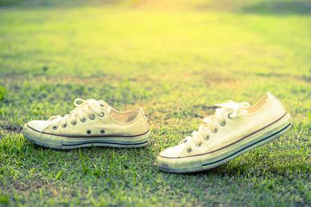 white sneakers on green grass