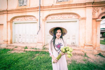 ベトナム文化長屋門ドレス、アオザイの保持蓮と美しい女性 写真素材