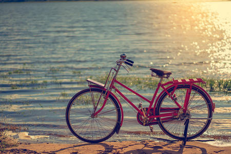 beside: red bicycle beside the river with blue sky Stock Photo