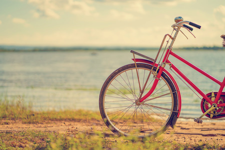 red bicycle beside the river with blue sky Stock Photo