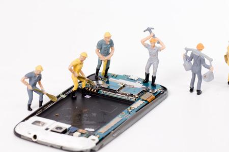 miniature people repair smartphone crack Stock Photo