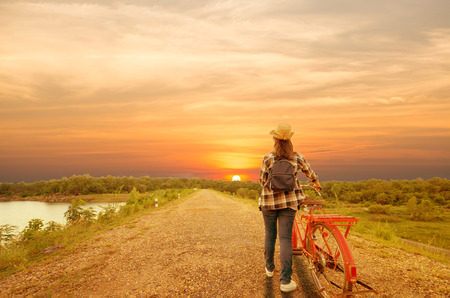 woman with red bicycle with sunset