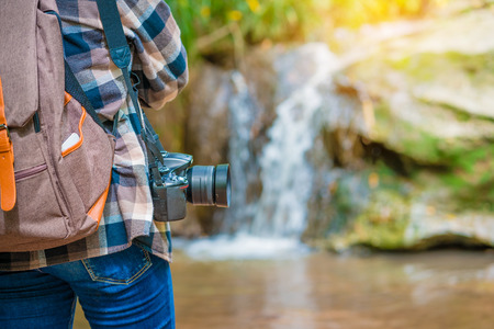 close up of camera with  woman tourist on the background of waterfall Stock Photo