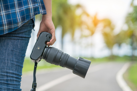 beside: photographer holding camera with nature background