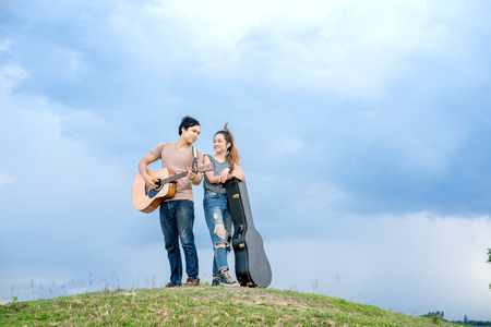 couple standing on the hill and play acoustic guitar with blue sky background