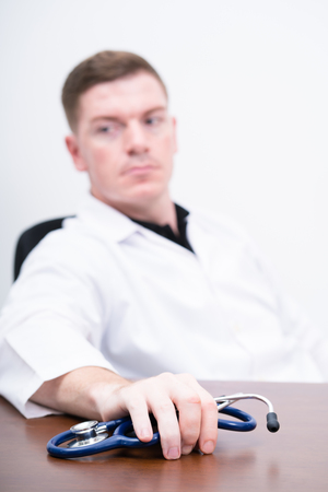 impersonal: caucasian man doctor holding  stethoscope on the table,selective focus Stock Photo