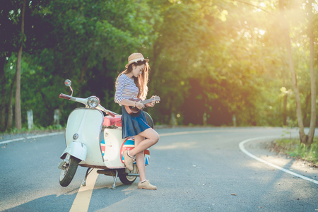 tourist playing ukulele and Vespa scooter on roadway