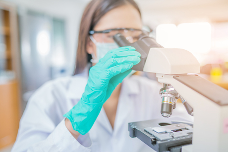 Doctor woman or chemist working with  microscope in laboratory room