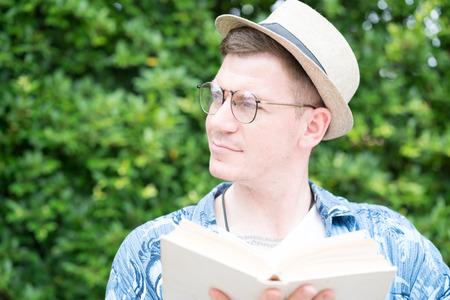 caucasian man eading book  in the garden