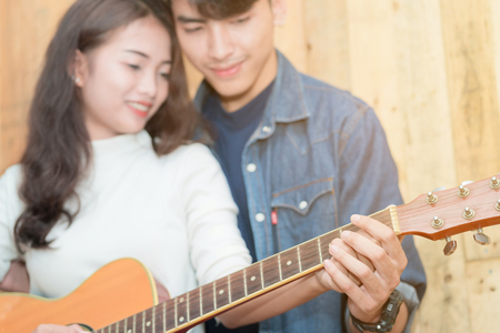 asian couple playing acoustic guitar