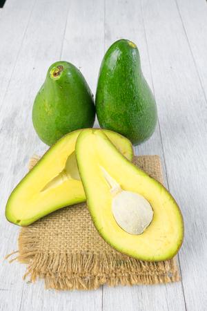 green avocado on wooden background Stock Photo