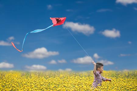 niños asiáticos jugando a la cometa en el campo de flor amarilla Foto de archivo