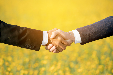 Close up hands of businessman shaking hands on yellow field