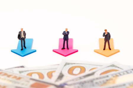 Miniature people,Businessman leader standing on arrow and us dollar banknote infront of,business concept
