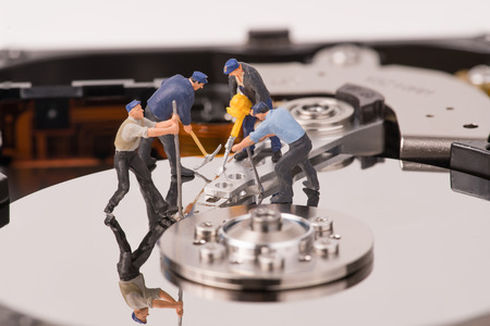 technicial team miniature people repairing  hard drive. Figures of people. The team of employees