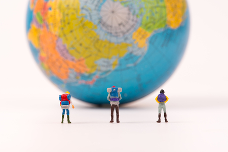 Miniature figure person backpack team, travelers standing with world globe, tourism concept Stock Photo
