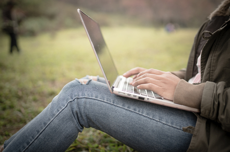 close up woman hands using laptop in the park Stock Photo