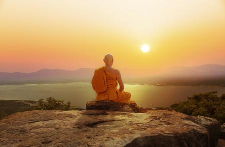 Buddhistischer Mönch in der Meditation bei schönem Sonnenuntergang oder Sonnenaufganghintergrund auf hohem Berg