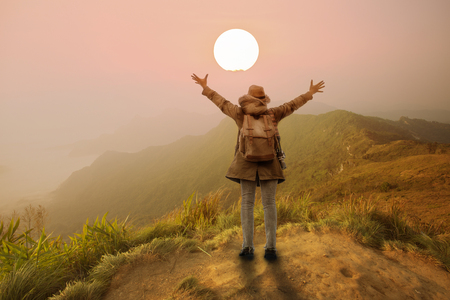backpacker woman open hand in mountain with sunset or sunrise background