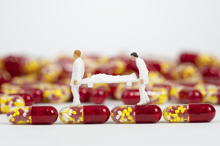 Miniature people with medical drug capsule on white background