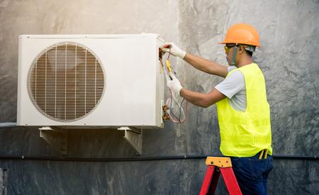 aziatische man voert het koelmiddel van de airconditioning uit de tank Stockfoto