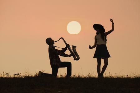 Músico tocar el saxofón con fondo de puesta de sol o amanecer Foto de archivo