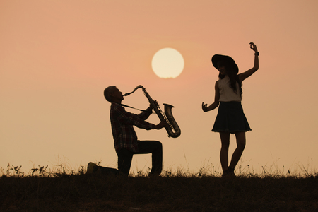 musician play saxophone with sunset or sunrise background Stock Photo