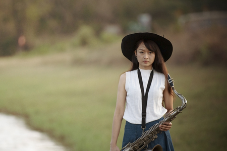 Woman with saxophone with nature background